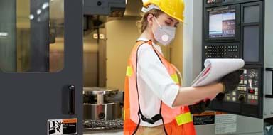 A female supervisor/operator in a factory is checking on a terminal of milling machine
