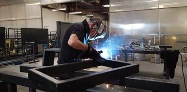 Fabricator welding steel frame at Abbey Group