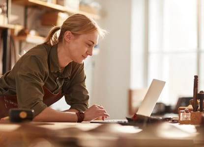 Warm toned portrait of successful female artisan using laptop in crafting workshop, copy space