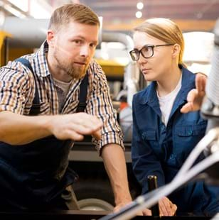One of young confident technicians pointing at mechanism of industrial equipment during discussion of its qualities with colleague