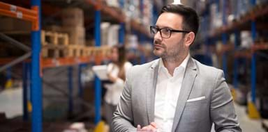 Successful businessman manager CEO holding tablet and walking through warehouse storage area looking towards shelves.