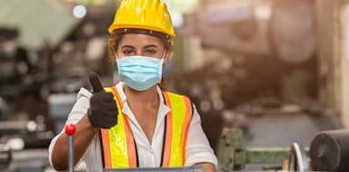 Female factory worker wears a disposable face mask for protection of Corona Virus Spreading and smoke dust air pollution filter in a factory.