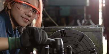 Certified industry female mechanical engineer working on industrial factory machinery - Skilled apprentice technician woman wearing safety equipment