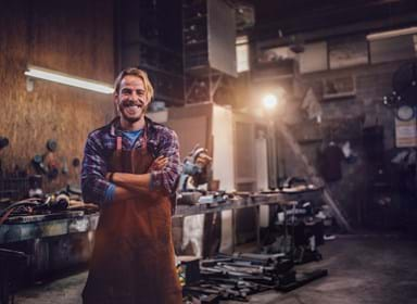 Portrait of smiling mechanic standing in garage workshop with professional equipment