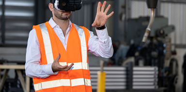 Male factory worker operating a robotic arm using a virtual reality headset