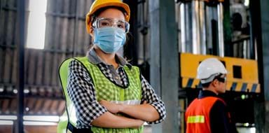 Factory woman worker or technician with hygienic mask stand with confident action with her co-worker as background.